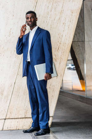 Young African American Businessman wearing blue suit, white undershirt, leather shoes, holding laptop computer, standing by column on street outside office in New York, talking on cell phone outside.