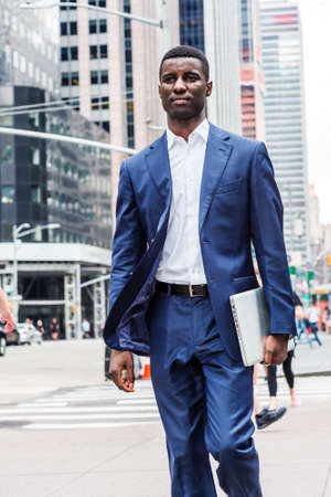 Young African American Businessman traveling in New York City, wearing blue suit, white undershirt, carrying laptop computer, walking on busy street with high buildings in Midtown of Manhattan.