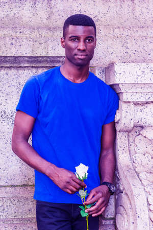 Young African American Man missing you in New York City, wearing blue short sleeve T shirt, standing in corner of vintage wall on campus, holding white rose flower, looking forward, waiting.