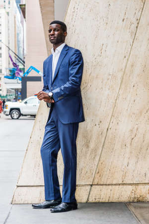 Portrait of Young African American Businessman in New York. Young Man wearing blue suit, white undershirt, leather shoes, wristwatch, standing by column on street outside office, waiting, looking.