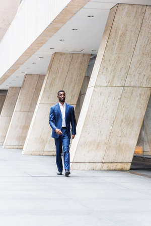 Young Handsome African American Businessman traveling, working in New York, wearing blue suit, white undershirt, leather shoes, holding laptop computer, walking on street outside office building.