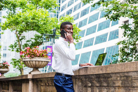 Young African American Man working in New York City, wearing white long sleeve shirt, blue pants, standing on campus, working on laptop computer on top of old style fence wall, calling on cell phone.