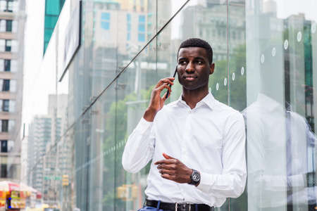 Young African American Man traveling in New York City, wearing white long sleeve shirt, wristwatch, standing against glass wall with reflections on street of Manhattan, talking on cell phone.
