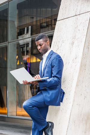Young African American Businessman working in New York City, wearing blue suit, white shirt, standing against column on street outside office building, looking down, reading on laptop computer.