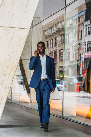 Young African American businessman talking on cell phone, traveling, working in New York, wearing blue suit, white undershirt, carrying laptop computer, walking out from office building to street.