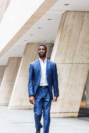 Young Handsome African American Businessman traveling, working in New York, wearing blue suit, white undershirt, holding laptop computer, walking on street outside office building, looking around.