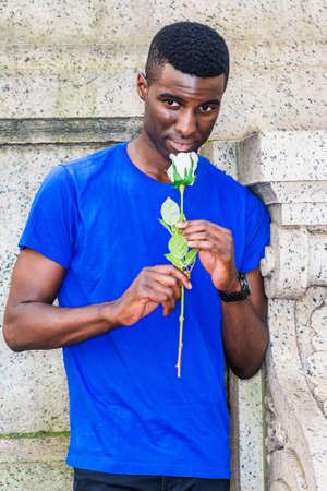 Young African American Man missing you in New York City, wearing blue short sleeve T shirt, standing in corner of vintage wall on campus, holding white rose flower, lowering head, smelling flower. 版權商用圖片