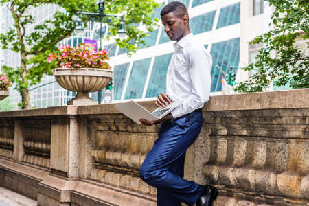 Young African American College Student studying in New York City, wearing white long sleeve shirt, blue pants, standing against half vintage wall on campus, looking down, working on laptop computer.