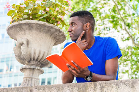 Young African American College Student studying in New York City, wearing blue short sleeve T shirt, standing, back bending forward on top of wall on campus, hand holding red book, reading, thinking 版權商用圖片