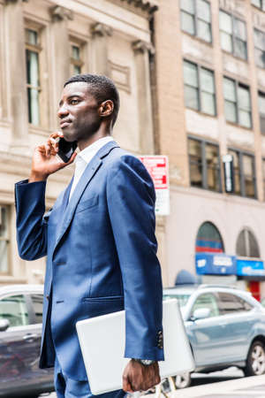 Young African American businessman talking on cell phone, traveling, working in New York, wearing blue suit, carrying laptop computer, walking on street in Manhattan. Cars, buildings on background. 版權商用圖片