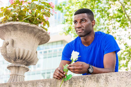 Young African American Man missing you in New York City, wearing blue short sleeve T shirt, wristwatch, standing, bending forward on top of wall, holding white rose, looking forward, waiting, thinking. 版權商用圖片