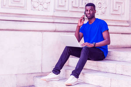 Young African American College Student studying in New York, wearing blue T shirt, black pants, sneakers, wristwatch, sitting on stairs on campus, working on laptop computer, talking on cell phone. Stockfoto
