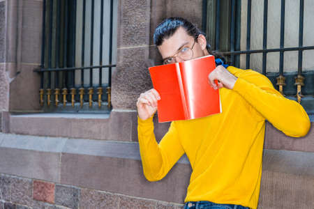 Young Hispanic American College Student reading red book outside in New York City, wearing glasses, yellow long sleeve T shirt, standing by wall with windows, holding red book over face, thinking.