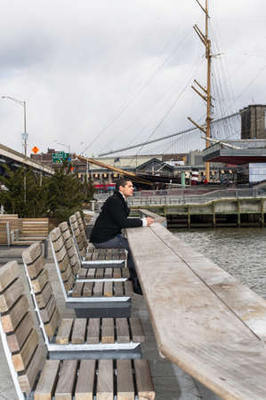 A young handsome guy is sitting by a harbor and waiting for you. Stockfoto