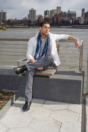 Back against  a big city outline, a young student is sitting by the river and thinking