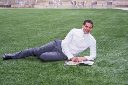 A young guy is lying on a lawn and reading.