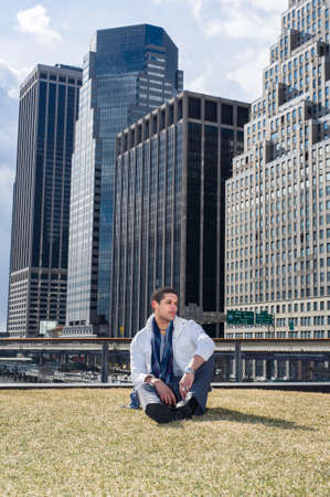 A young student is sitting on a lawn in the front of a business district and looking forward.