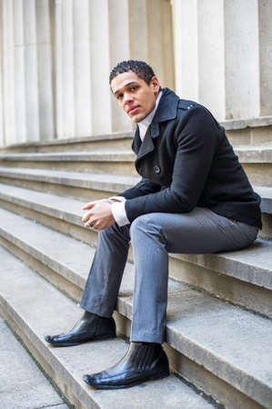 A handsome man is sitting on stairs in the front of a building and taking a break Stockfoto
