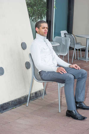 A young professional is sitting on a chair and taking a break outside
