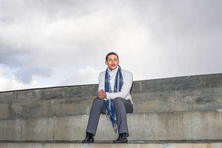 A young handsome guy is sitting outside on steps and thinking. Stockfoto - 165175014