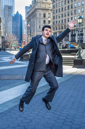A young businessman is cheerfully jump on street Stockfoto