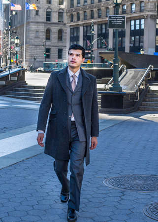 A young businessman is confidently walking outside