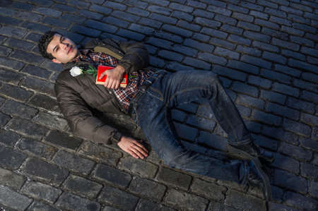 Holding a red book and a white rose a young handsome guy is romantically lying on the ground and eagerly looking up
