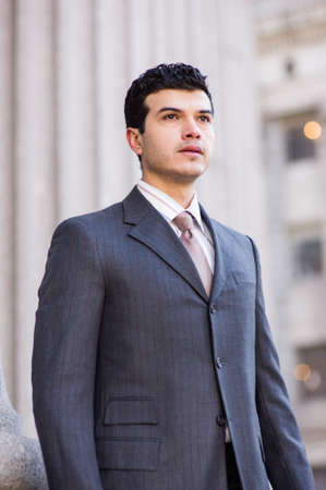 Dressing formally a young businessman is standing outside and looking forward Stockfoto