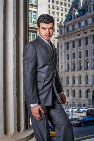 Dressing formally a young businessman is standing in the front of a office building and looking at you
