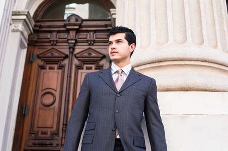 Dressing formally a young businessman is standing in the front of a office building and looking forward. The suit is a new style.
