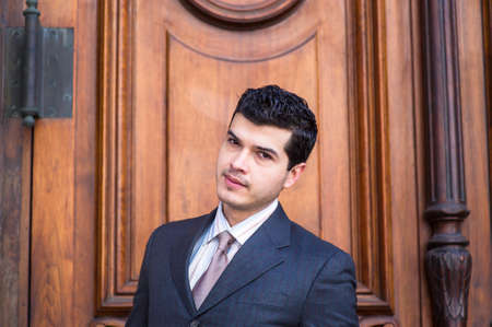 Dressing formally a young businessman is standing in the front of a office and looking at you Stockfoto