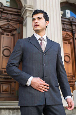Dressing formally a young businessman is standing in the front of a office building and looking forward. Stockfoto