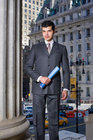 A young businessman is holding documents in the front of a office building and looking at you Stockfoto