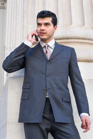 A young businessman is standing outside and talking on the phone Stockfoto