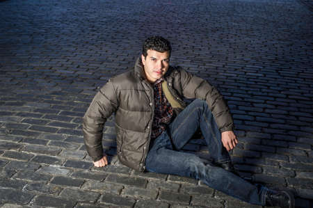 A young handsome guy is sitting on the ground in the dark