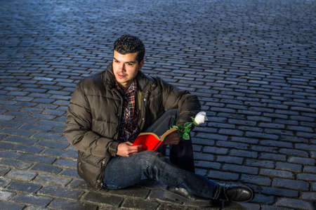 Holding a white rose and red book a young guy is reading outside