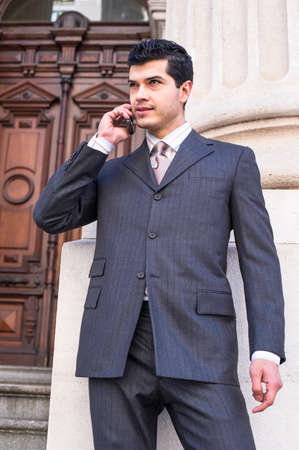 A young businessman is standing in the front of a office building and talking on the phone