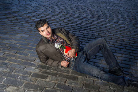 Holding a red book and a white rose a young handsome guy is romantically lying on the ground and eagerly looking around Stockfoto