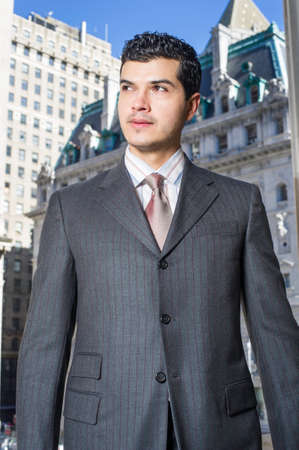 Dressing formally a young businessman is standing in the front of a business district and looking forward