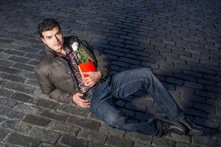 Holding a red book and a white rose a young handsome guy is romantically lying on the ground and eagerly looking at you