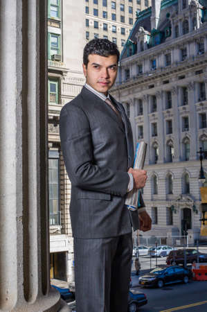 A young businessman is holding documents in the front of a office building and looking forward Stockfoto