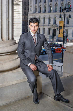 A young businessman is sitting outside and take a break