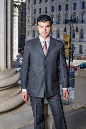 A young businessman is standing outside and looking at you Stockfoto