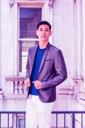 Portrait of Young Asian American College Student in New York, wearing gray blazer, blue undershirt, white pants, standing in old style office building on campus, looking forward. Color filtered effect