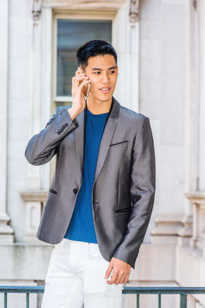 Young Asian American Male College Student talking on cell phone inside old style office building in New York City, wearing gray fashionable blazer, blue undershirt, white pants, standing on campus.