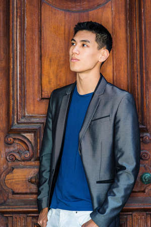 Portrait of Young Asian American Businessman in New York City, wearing in fashionable gray blazer, blue undershirt, white pants, standing by old fashion style office door, looking up, thinking.