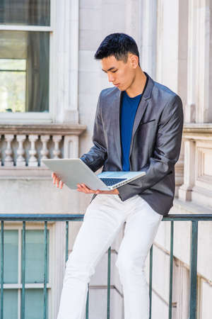 Young Asian American College Student studying, working in New York City, wearing gray blazer, white pants, sitting on railing on old style office building, looking down, working on laptop computer.