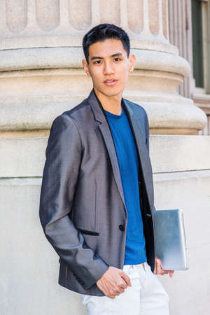 Young Asian American Businessman working in New York City, wearing gray blazer, blue undershirt, white pants, holding laptop computer, standing by column of old style office building, looking forward.