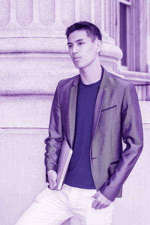 Young Asian American Man working in New York City, wearing gray blazer, blue undershirt, white pants, holding laptop computer, standing by column of old style office building. Color filtered effect.