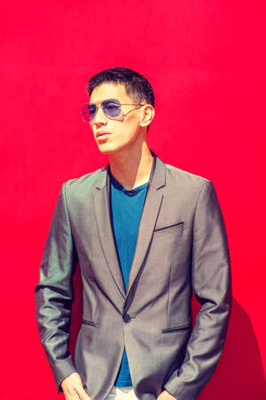 Portrait of Young Asian American Man in New York City, dressing in fashionable gray blazer, blue undershirt, wearing blue sunglasses, standing against red background under sunshine, looking away.